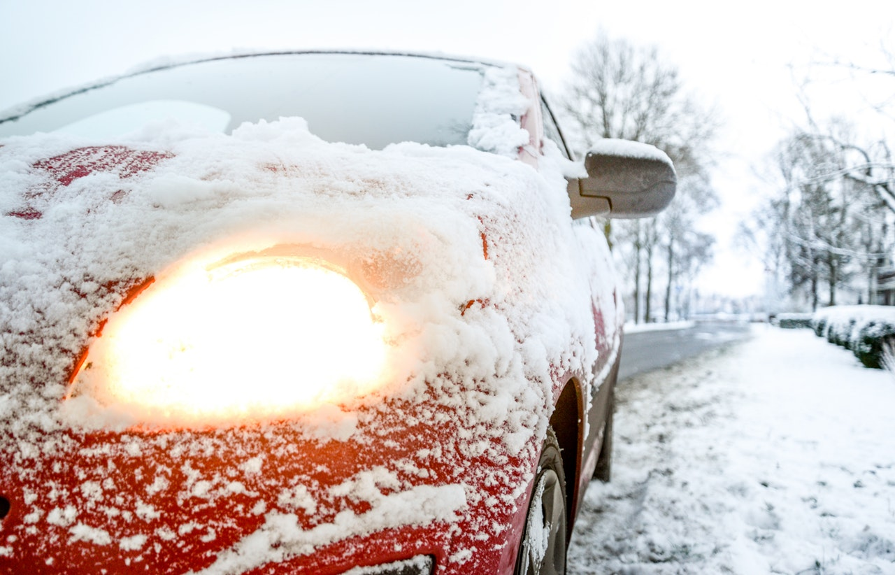 Image of a red car covered in snow. The car has its lights on, and has been serviced so that it is prepared to survive the winter weather.