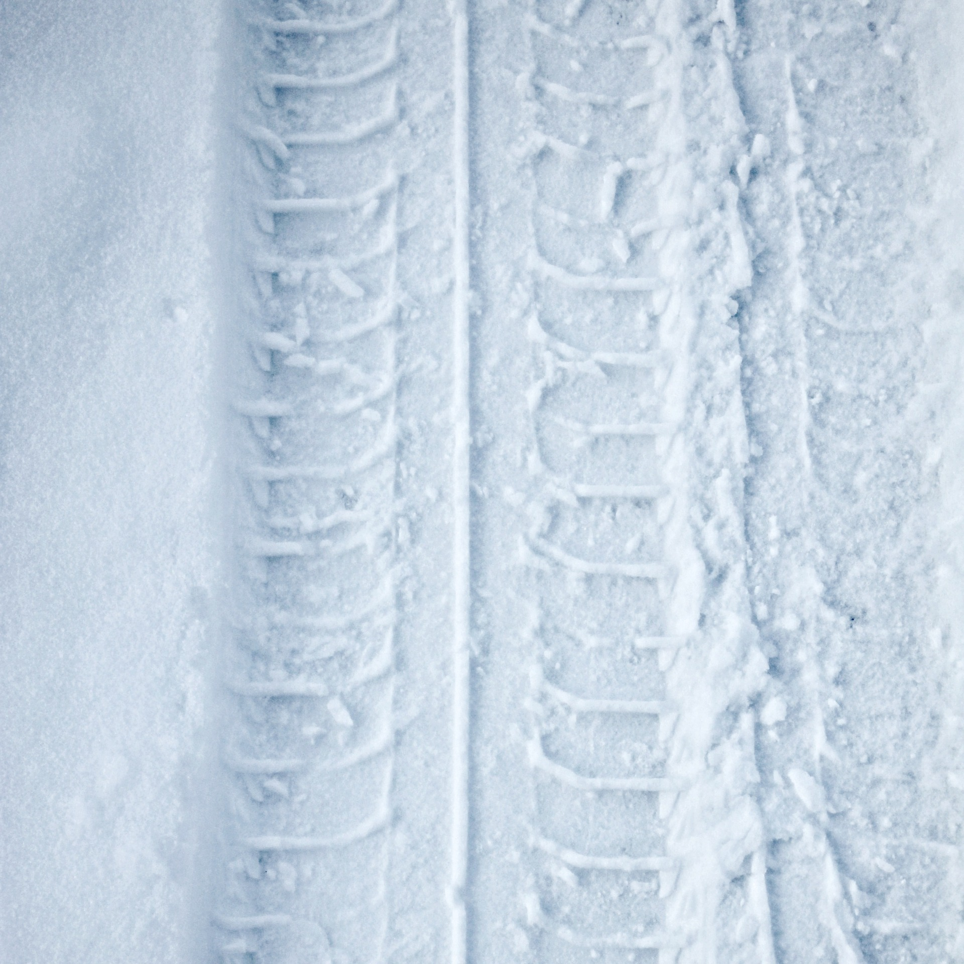 An image of a tyre track indented in the snow.