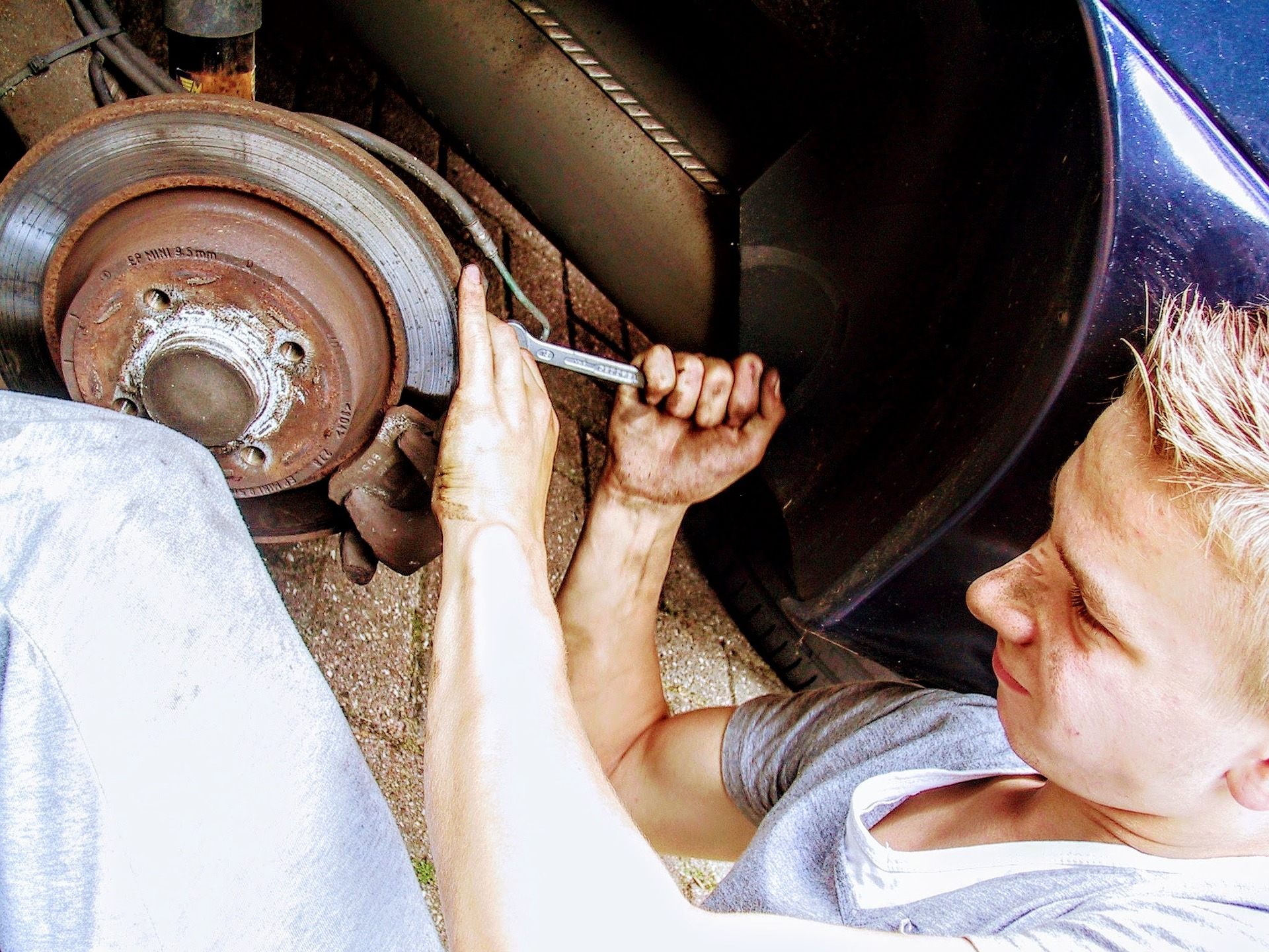 An image of a car mechanic fixing brakes.